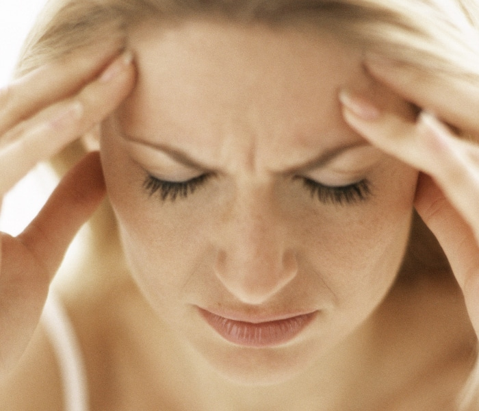 A woman struggling with a headache may need treatment for TMJ in Burke, VIrginia